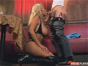 Bridgette B in steamy leather shoes and plumbs on a sofa